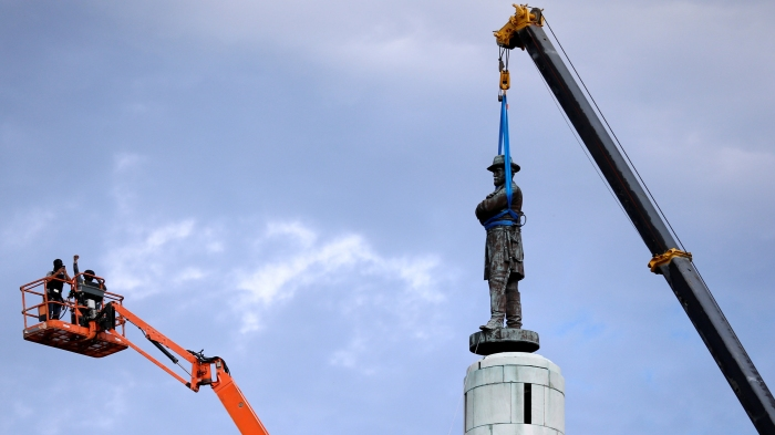A construction worker cheers as a monument of Robert E. Lee, who was a general in the Confederate Army, is removed in New Orleans
