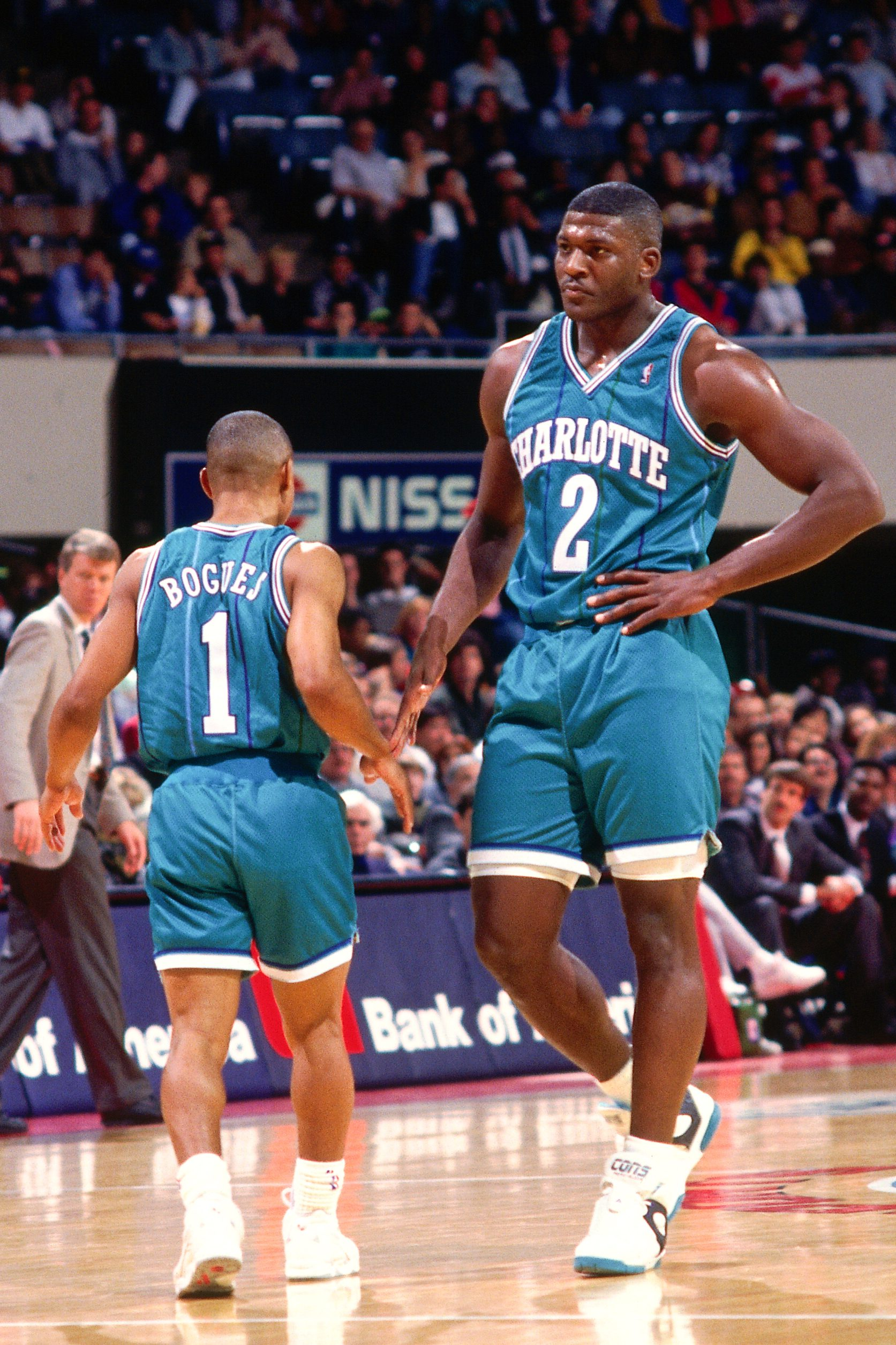 76e94f672ef07c 2) high-fives teammate Muggsy Bogues (No. 1) of the Charlotte Hornets  during a game against the New Jersey Nets played circa 1991 at Brendan  Byrne Arena in ...