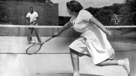 Louise Watson plays a tennis match against Norman Matlock at the West Park Courts in 1950