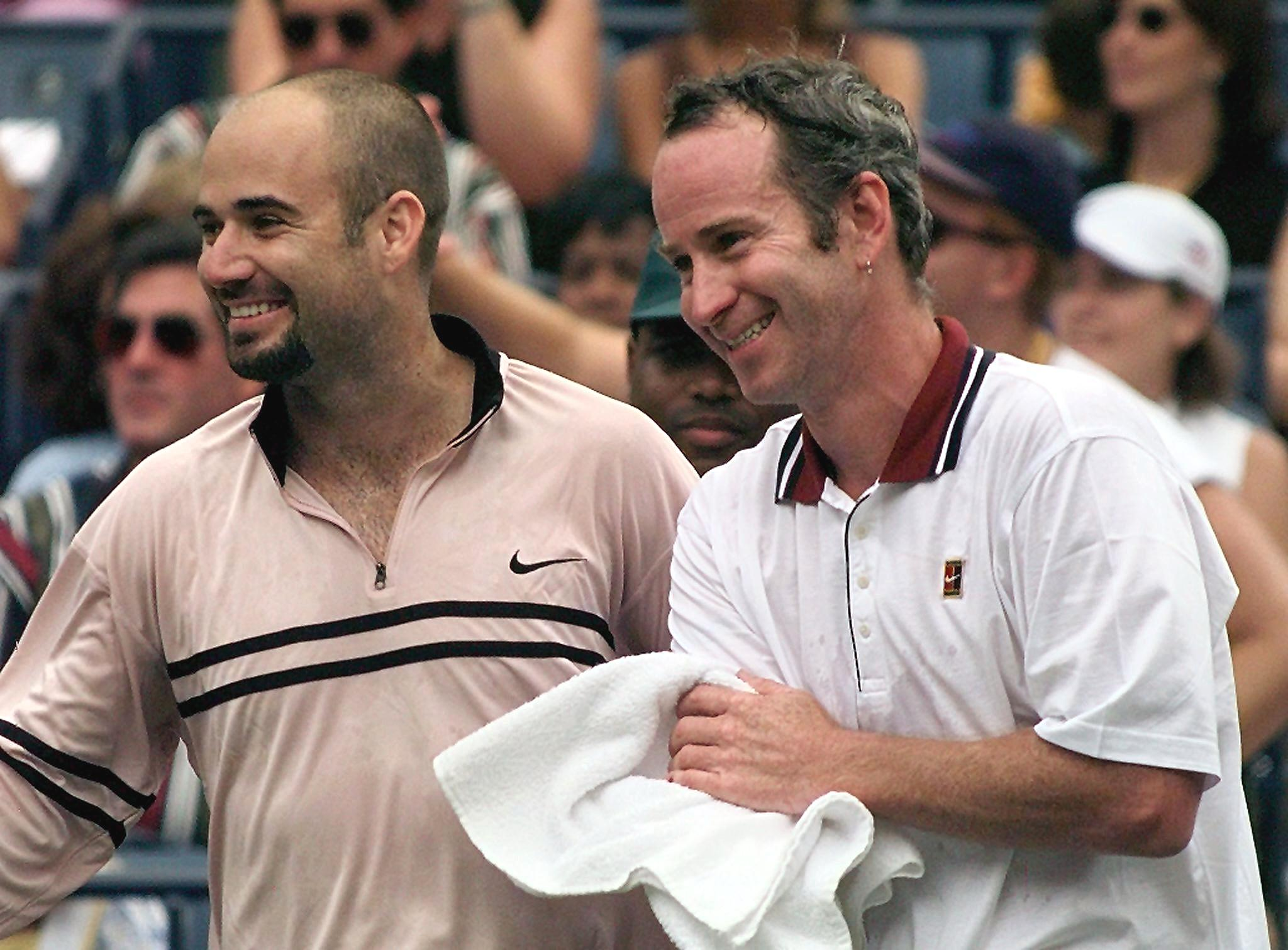 Andre Agassi (L) and John McEnroe laughing after a tennis match.