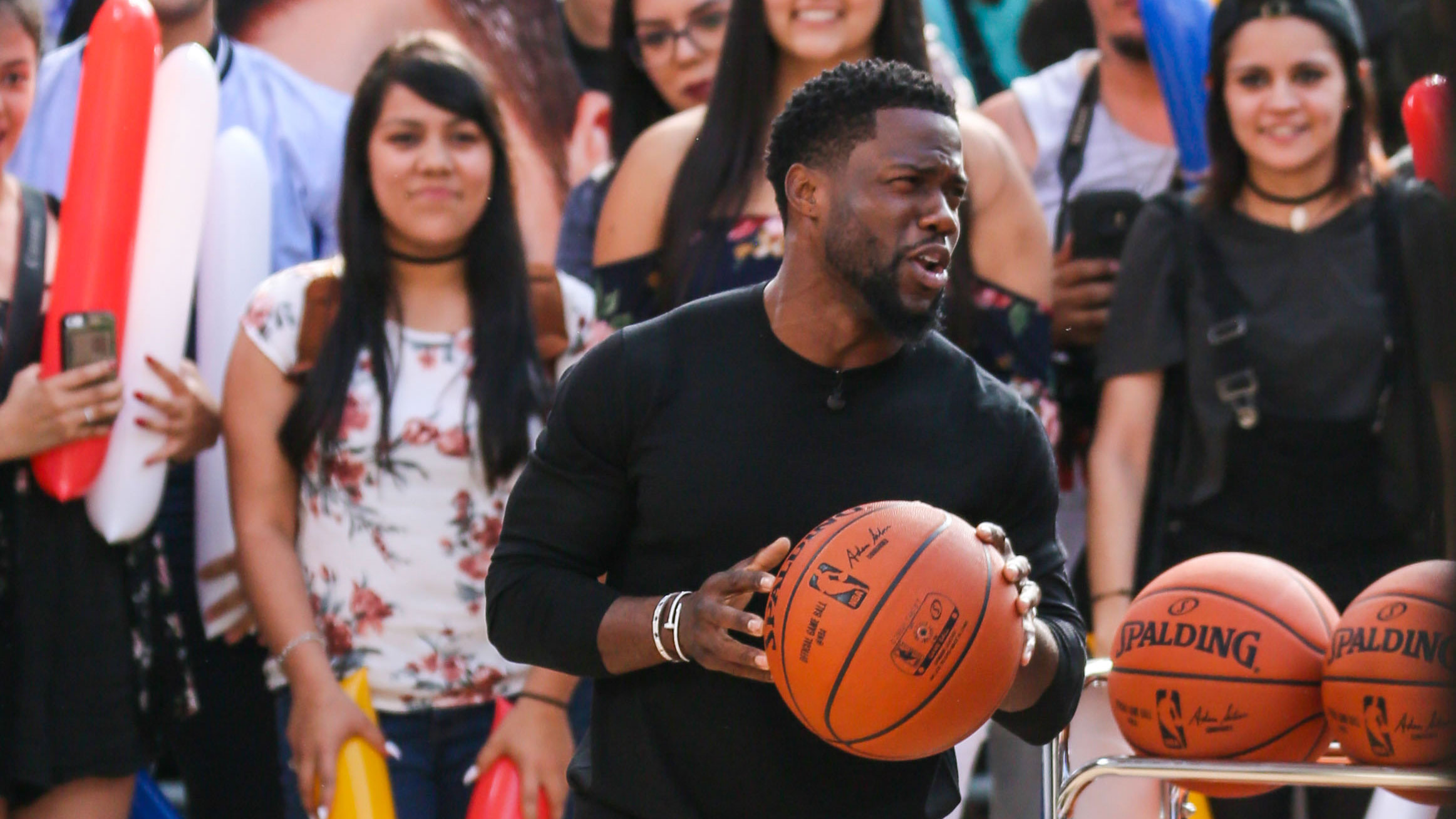 Kevin Hart holding a basketball on Jimmy Kimmel Live.