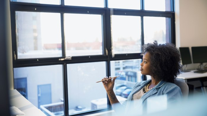 Pensive businesswoman looking out office window