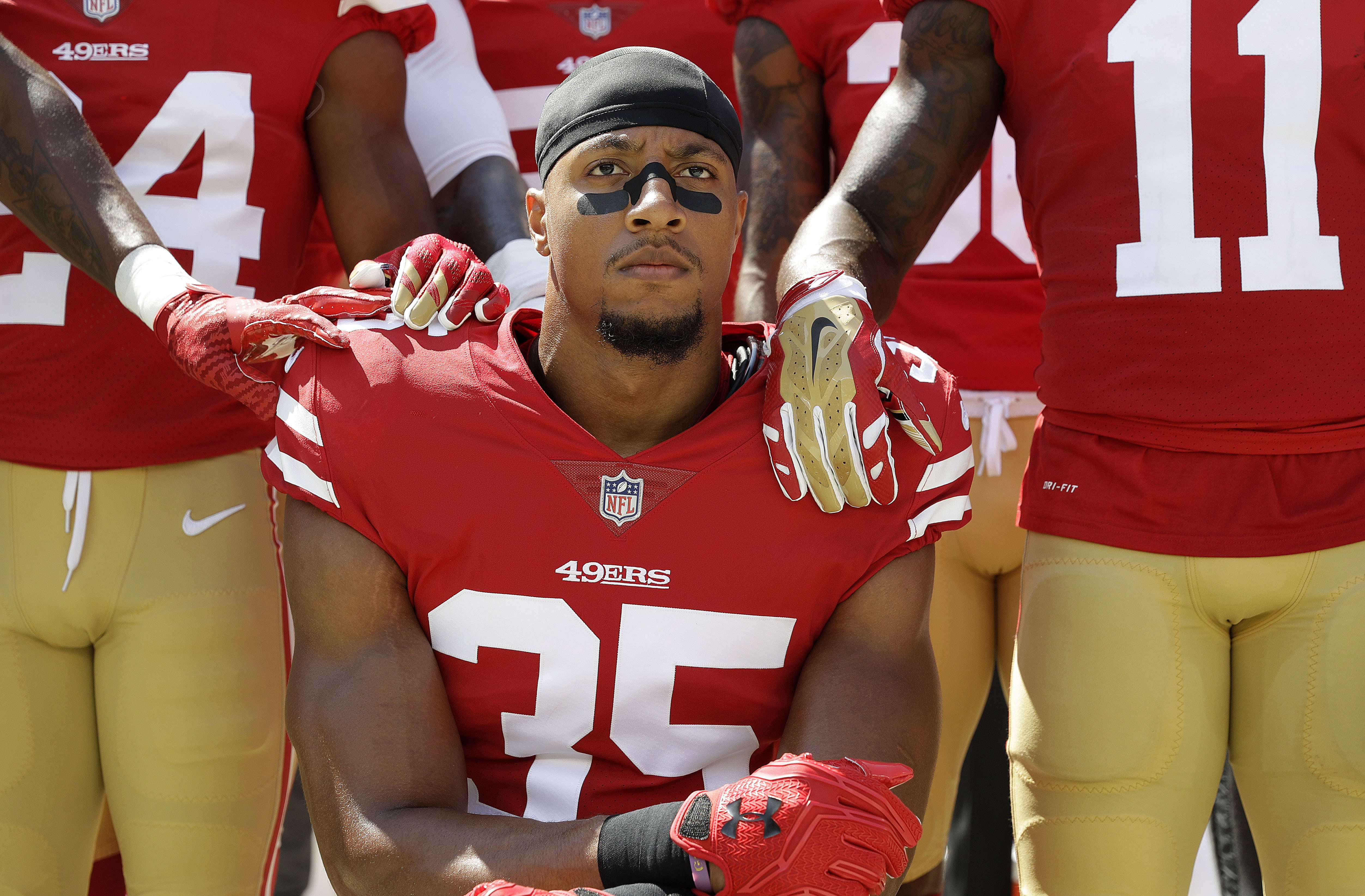 29d33cc0a19 San Francisco 49ers safety Eric Reid (35) kneels in front of teammates  during the playing of the national anthem before an NFL football game  between the ...
