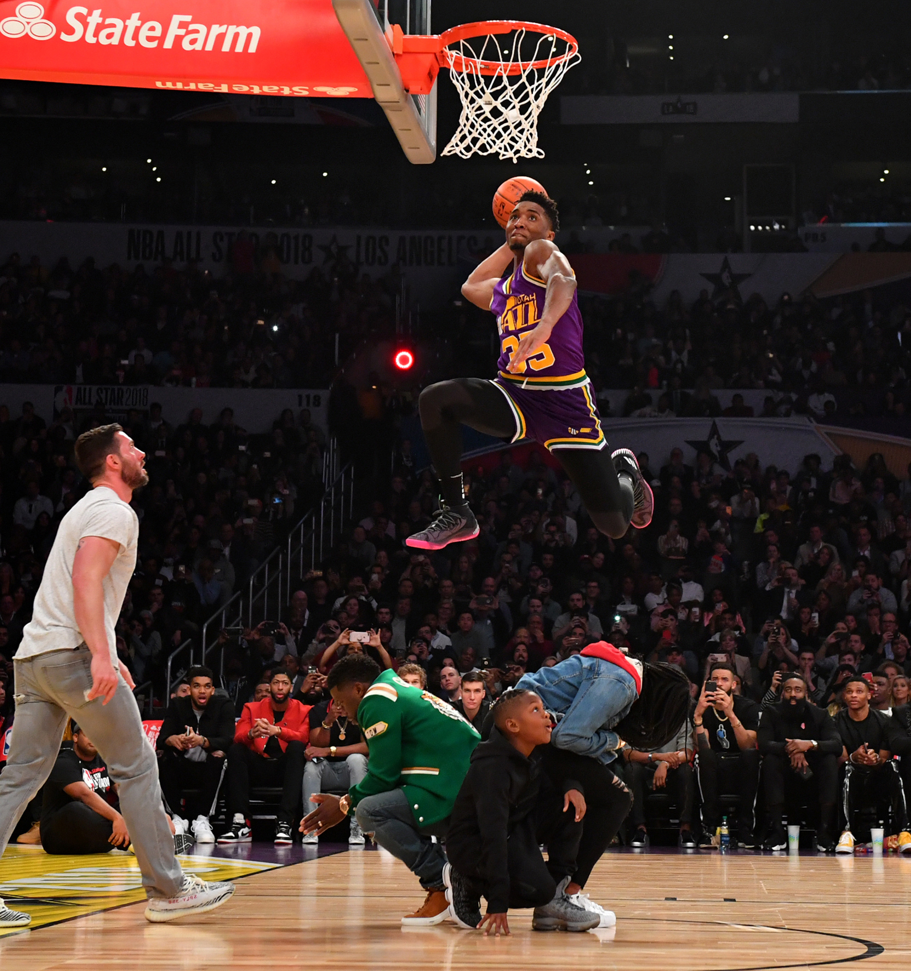 fd4d30326 Donovan Mitchell of the Utah Jazz dunks over Kevin Hart (center left) and  crew during the Verizon Slam Dunk Contest during State Farm All-Star  Saturday ...