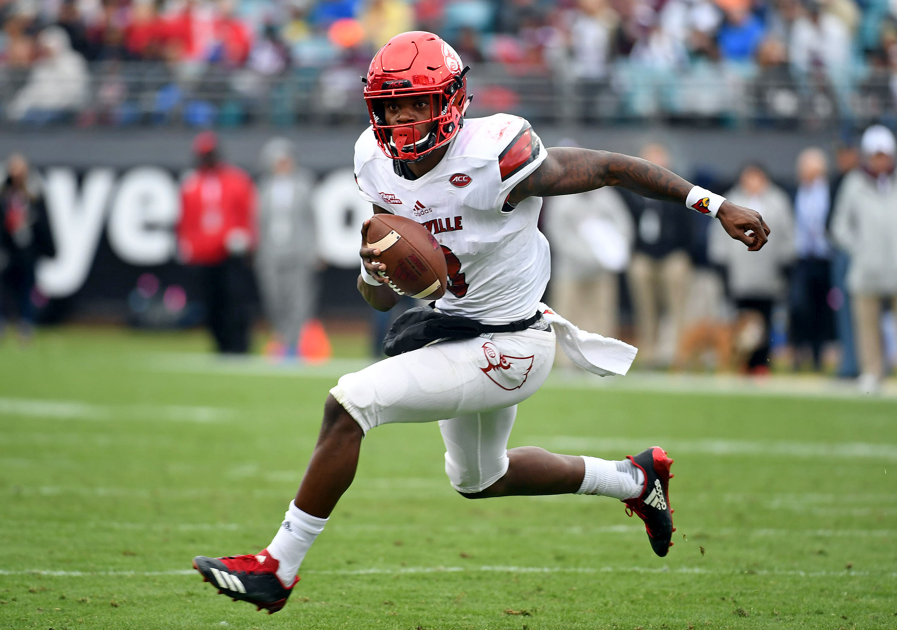 f5a4acae3 Louisville Cardinals quarterback Lamar Jackson runs for a touchdown during  the first half against the Mississippi State Bulldogs in the 2017 TaxSlayer  Bowl ...