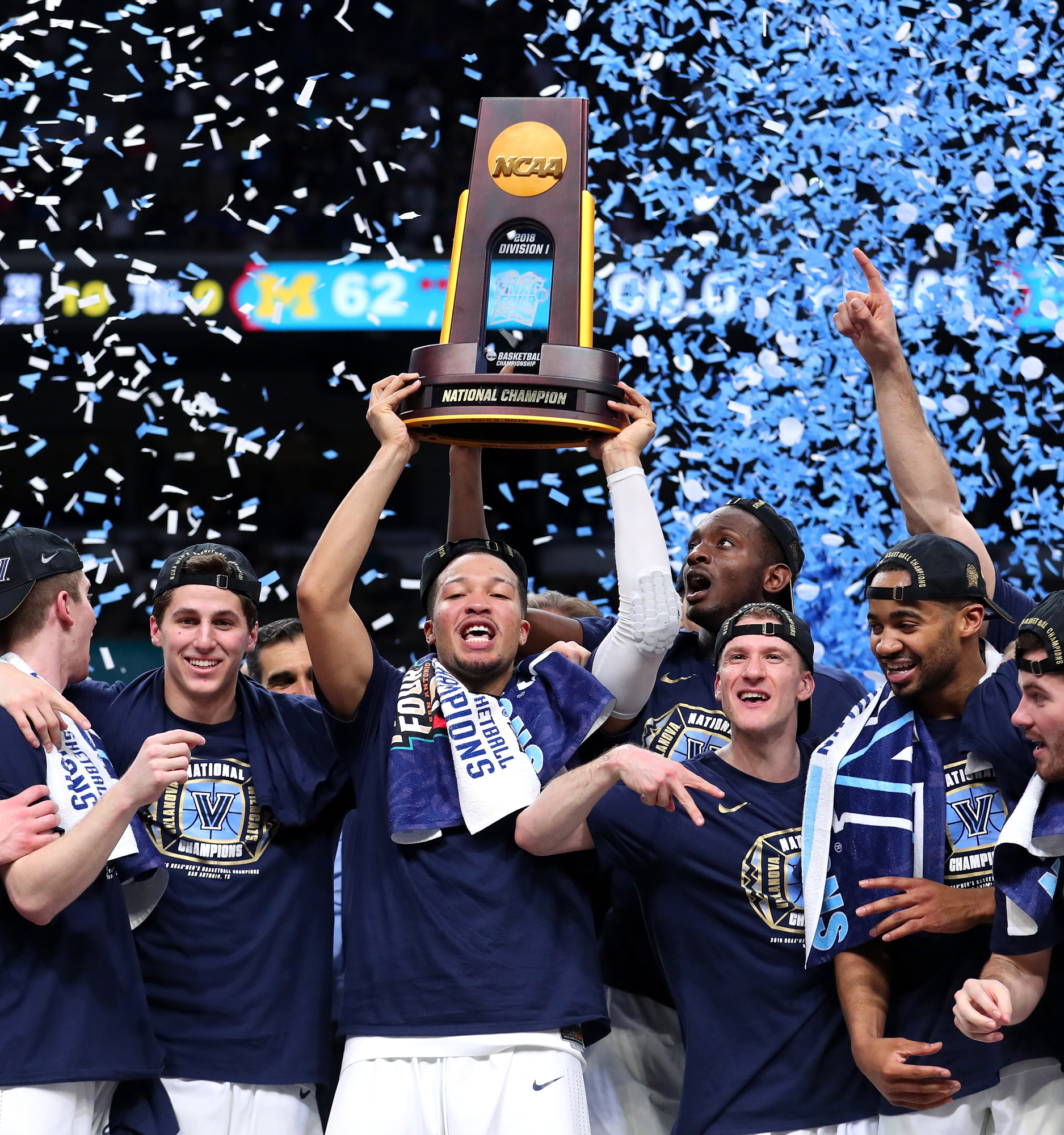 9d47bf7debd4 Jalen Brunson (center) of the Villanova Wildcats raises the trophy and  celebrates with his teammates after defeating the Michigan Wolverines  during the 2018 ...
