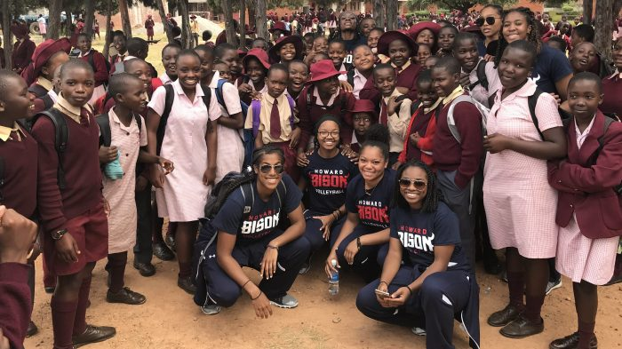 Howard University women's volleyball players with students at African school