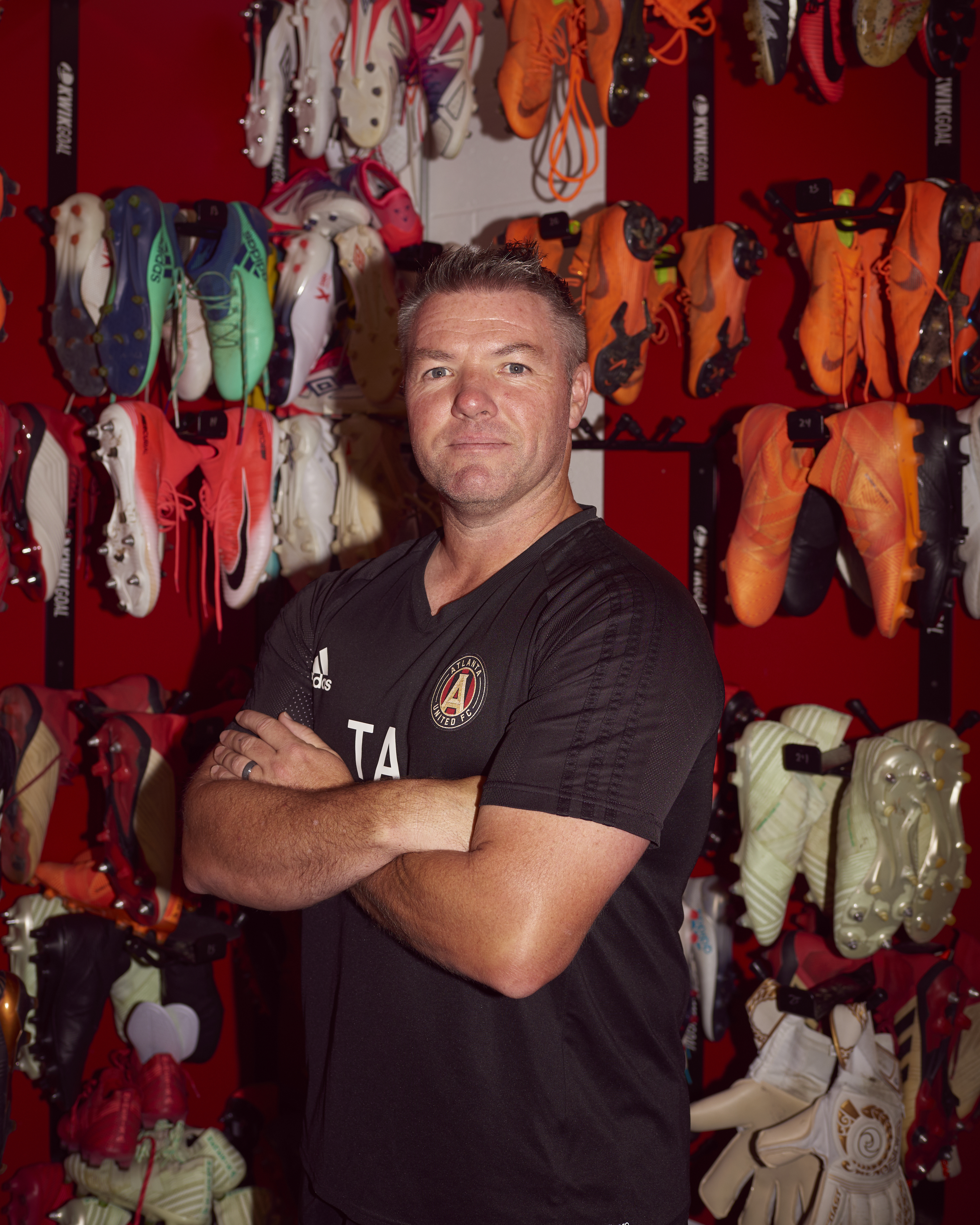 """98253a18b Tony Annan, Atlanta United academy director and U17 head coach, poses for a  portrait in the club """"boot room"""" on June 5."""