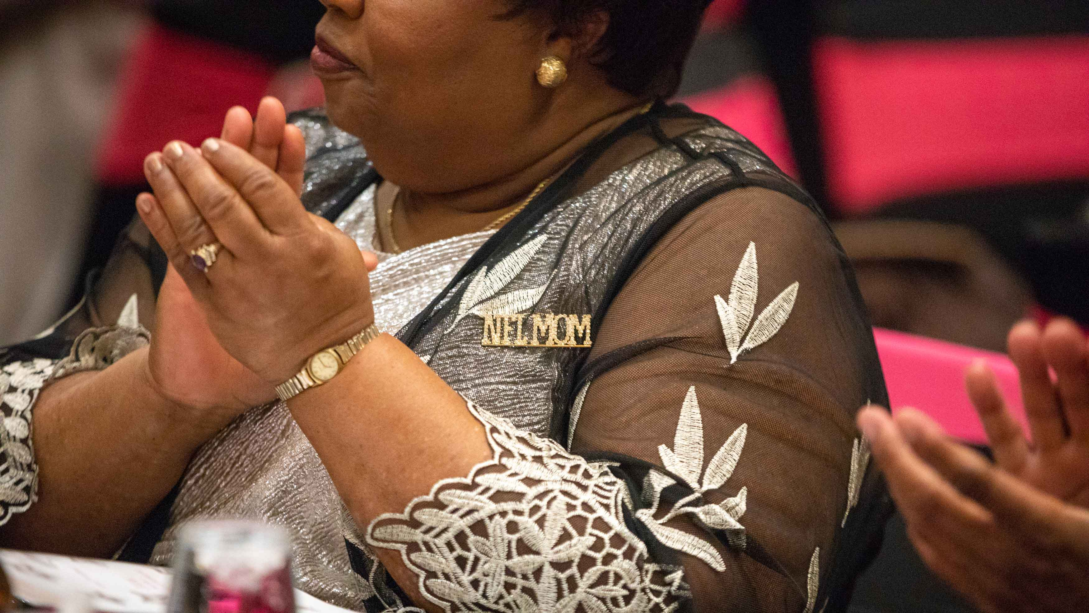 """Juanita Stevens, wearing an """"NFL MOM"""" pin, at a dinner table during the party."""