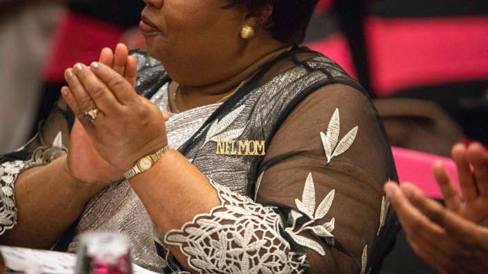 "Juanita Stevens, wearing an ""NFL MOM"" pin, at a dinner table during the party."