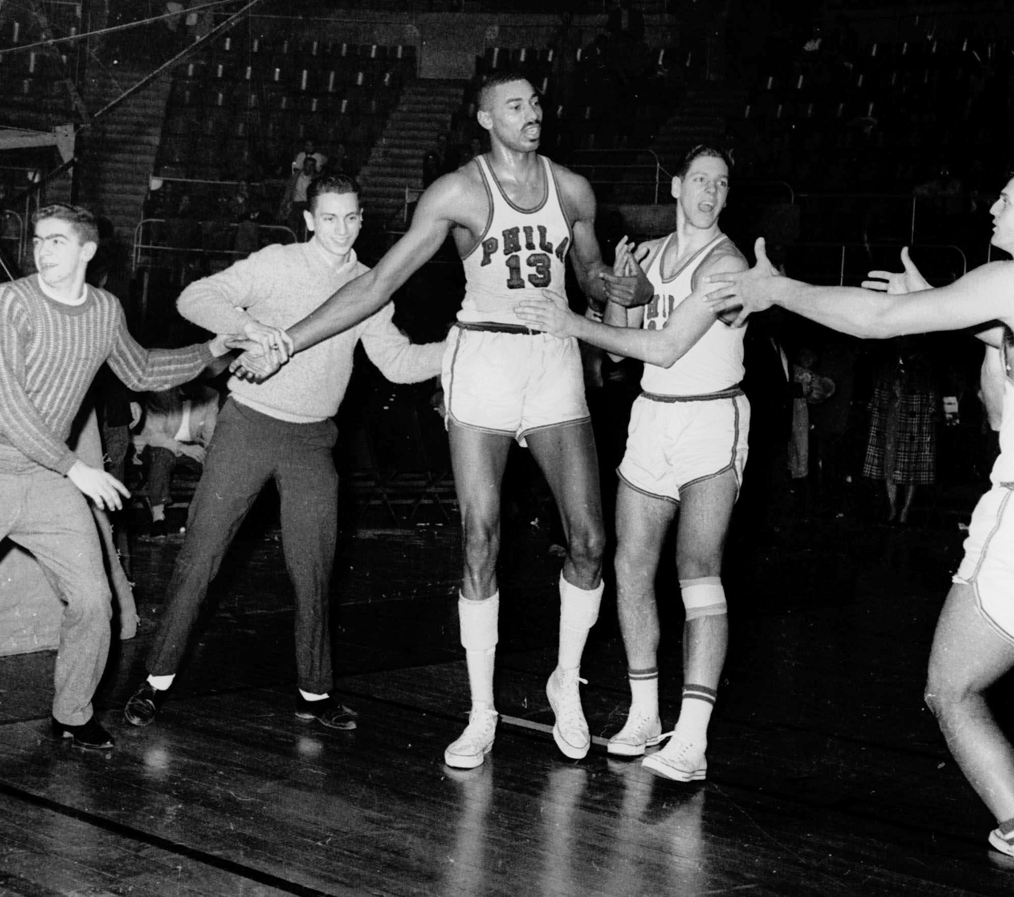 9c4f10f6a06e Fans and teammates rush onto the court to congratulate the Philadelphia  Warriors  Wilt Chamberlain (center) in Hershey