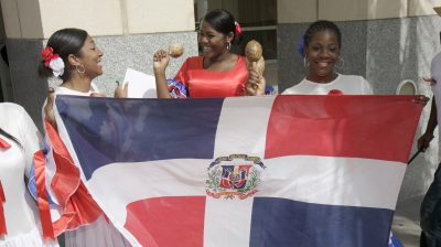 Women holding a Dominican Republic flag at the Miami Book Fair International parade.