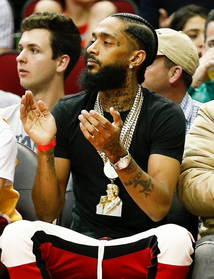 size 40 a4098 08f61 Nipsey Hussle watches from courtside at the Toyota Center in Houston on  March 3, 2018.